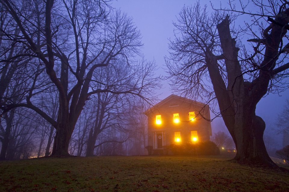 Old stone house with candles in window on foggy gloomy night