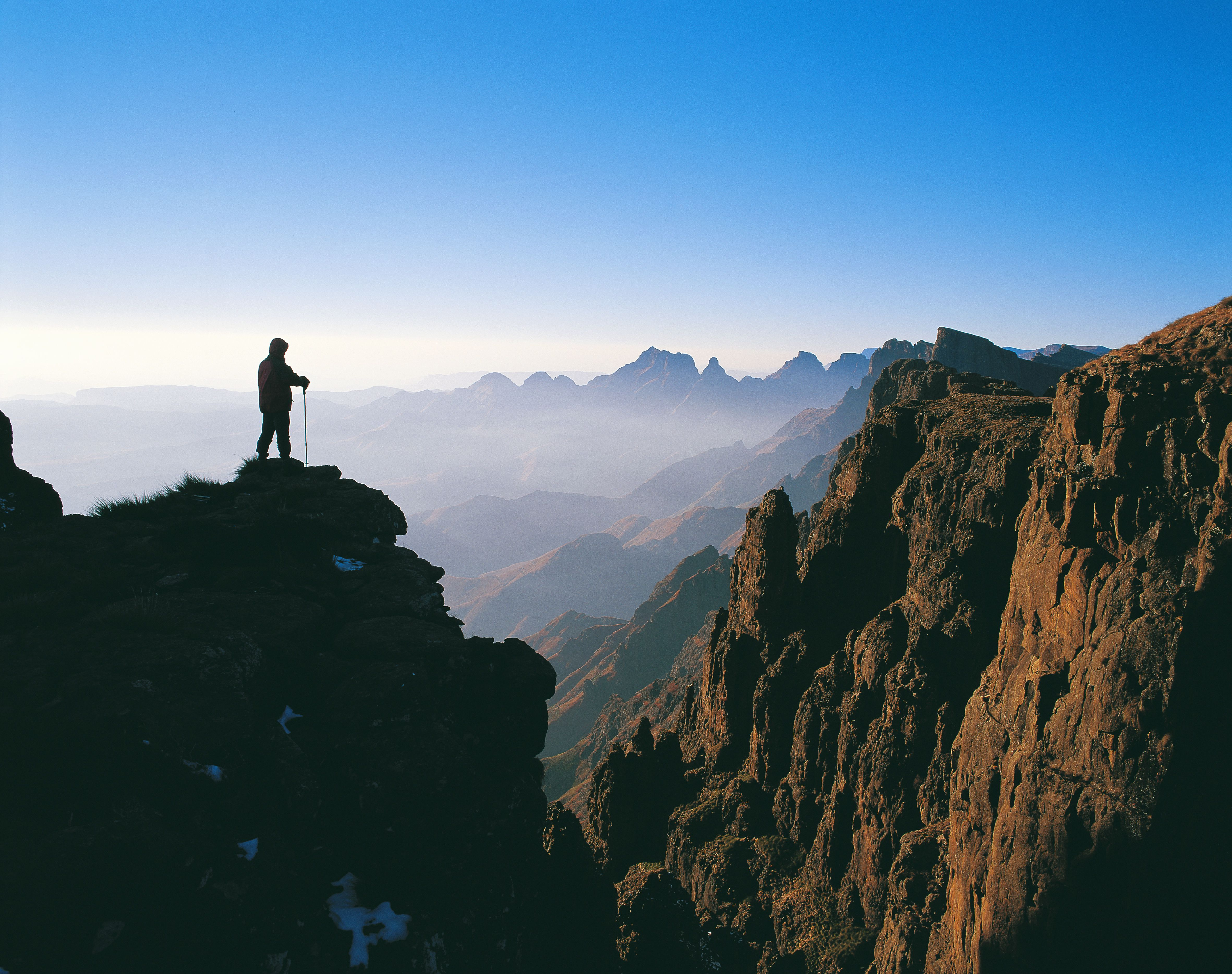 Silhouette of a Hiker Overlooking a Misty Mountain Range