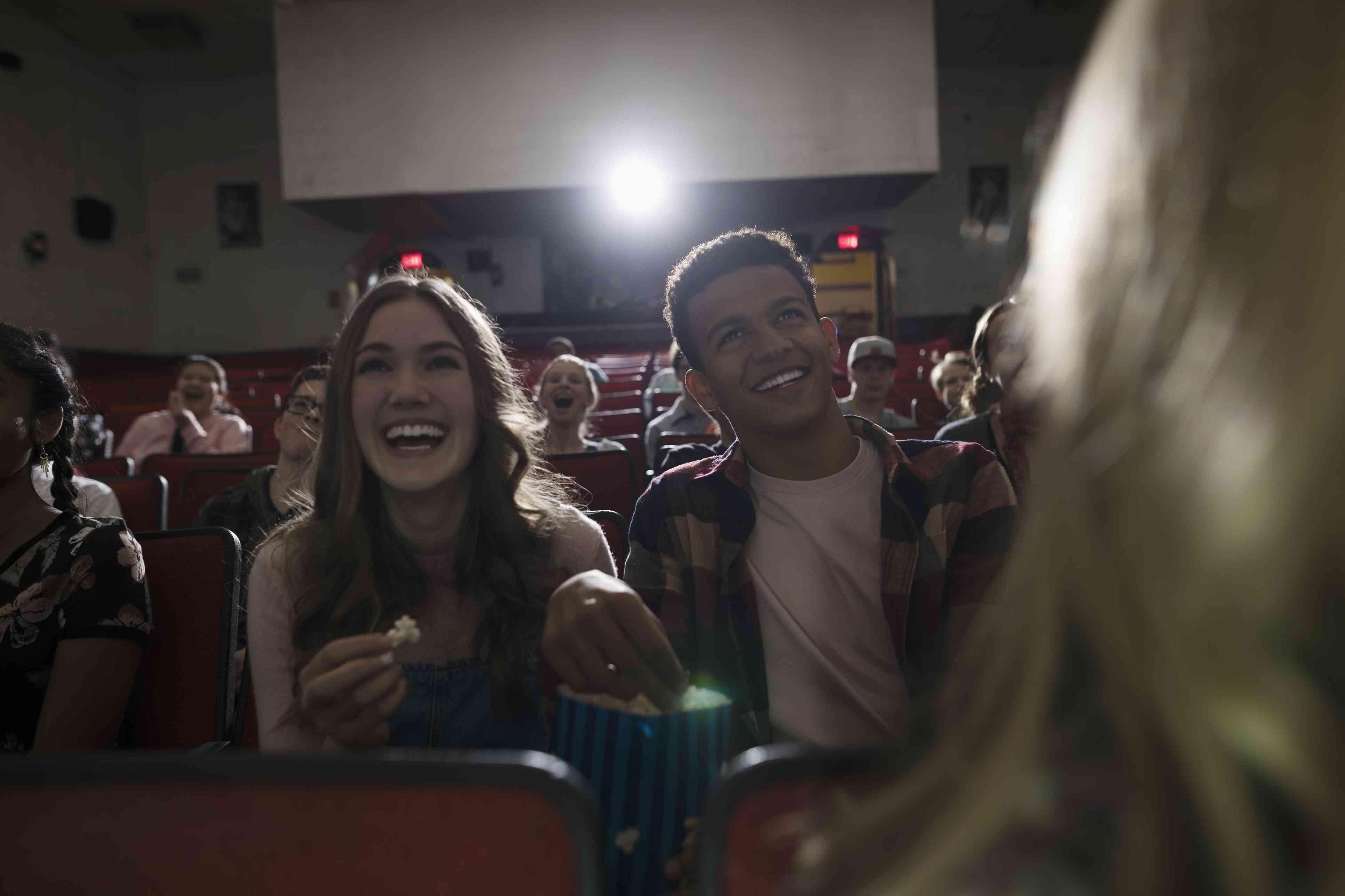 Pareja de adolescentes entre risas comiendo palomitas de maíz, viendo películas en el cine oscuro