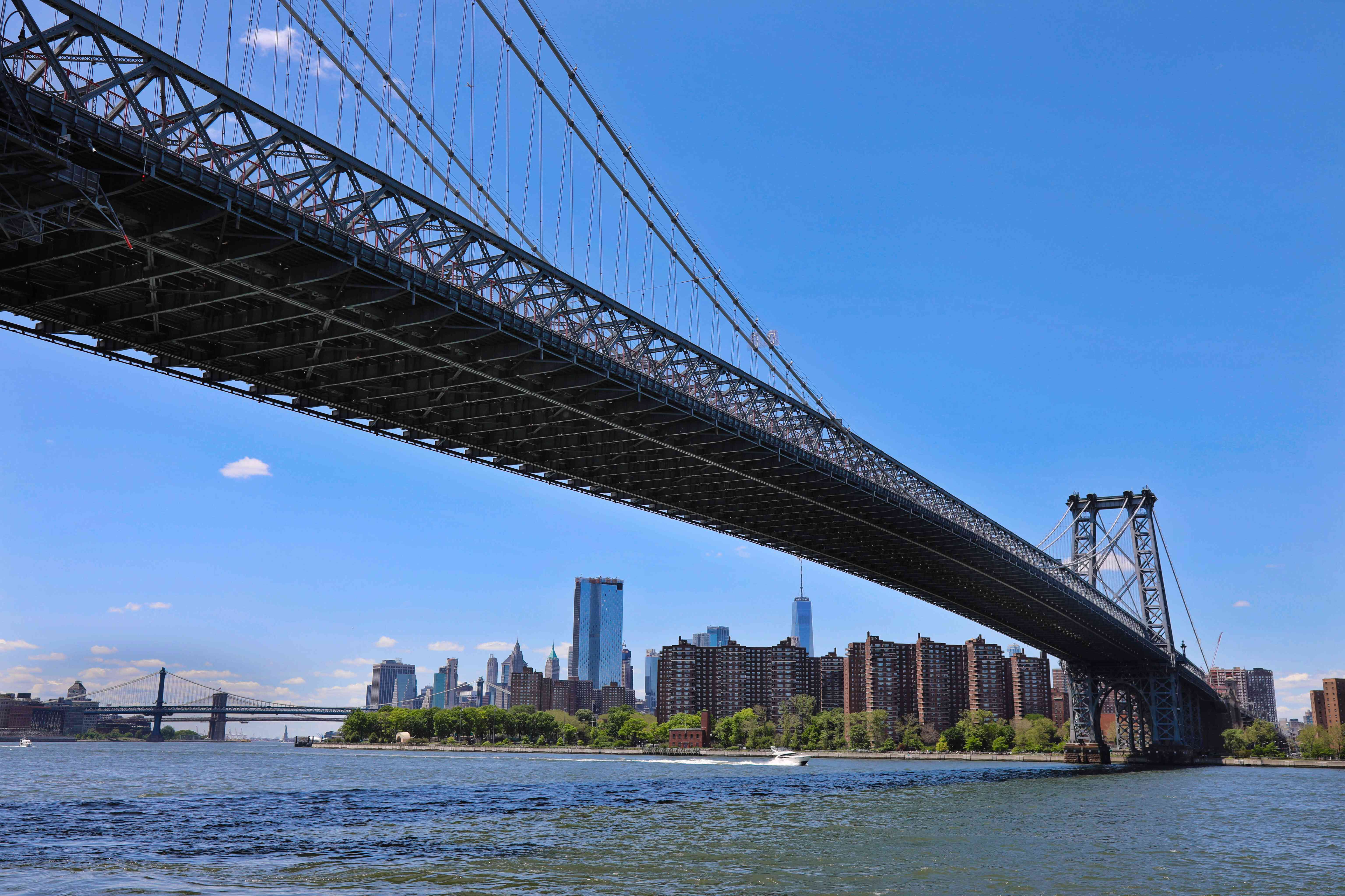 A bridge of the Williamsburg bridge stretching out across the water