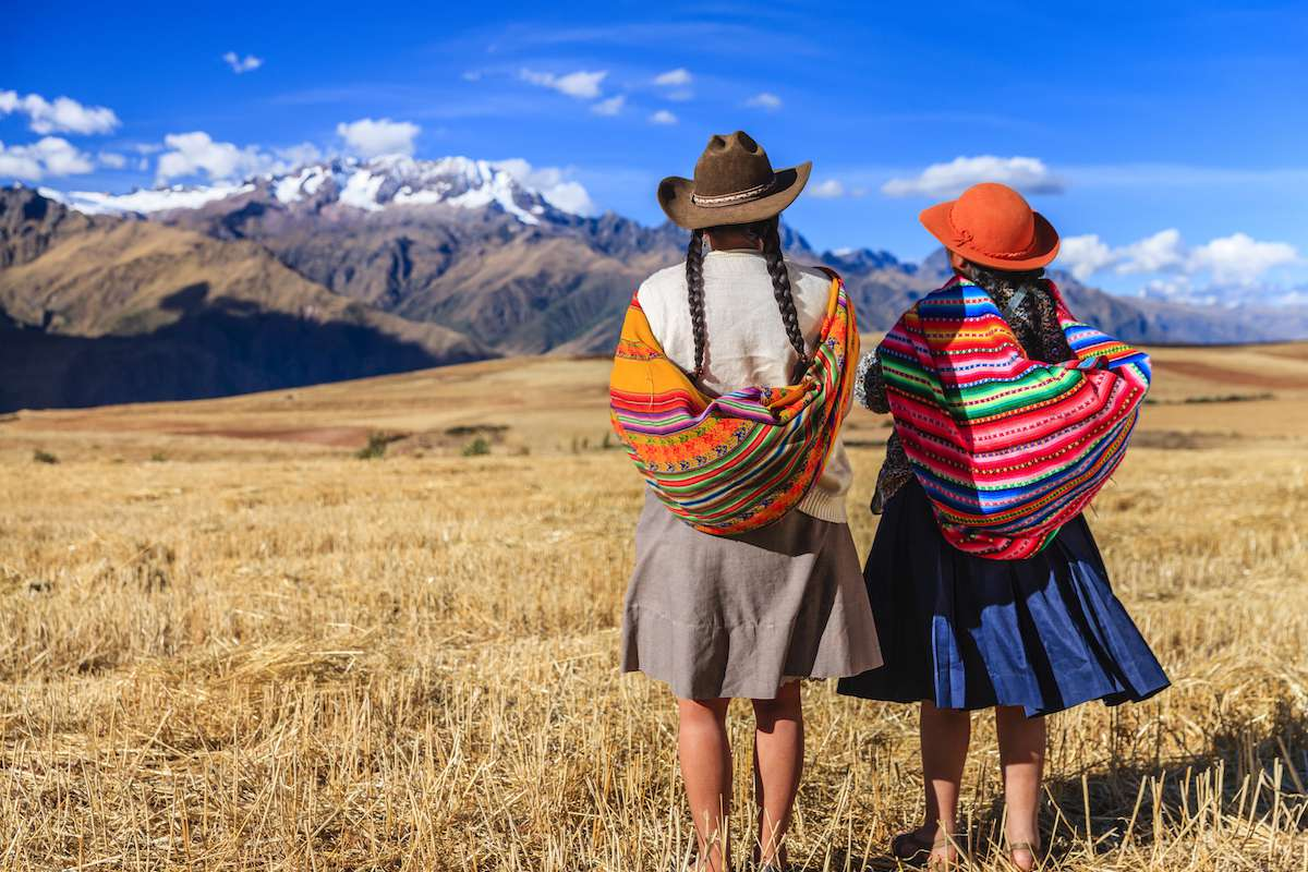 Two girls stand in a grassy field looking at the mountains in the distance.