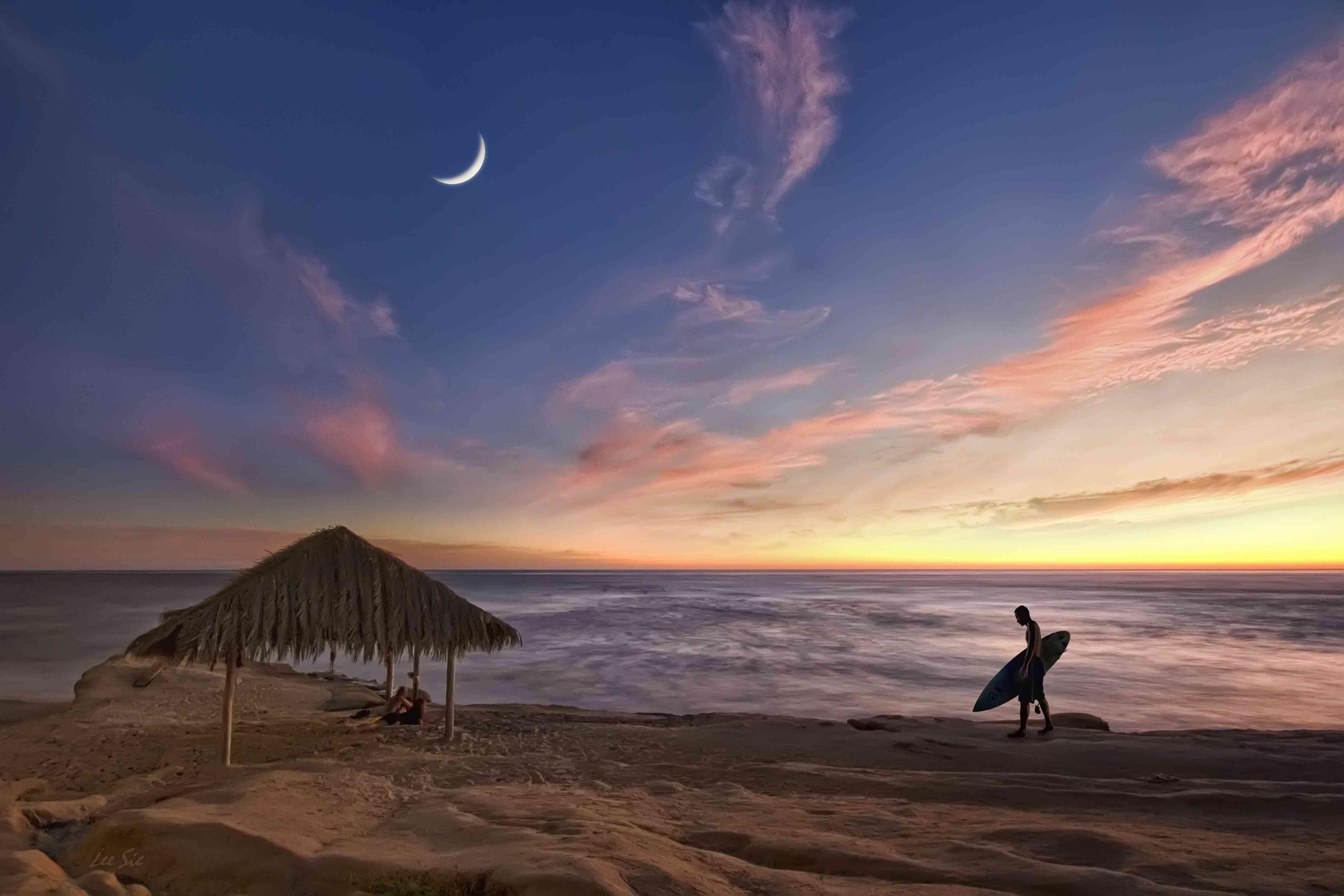 hombre con tabla de surf caminando en la playa de Windansea al atardecer