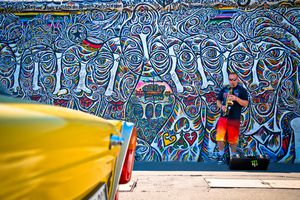 Street musician playing the saxophone along the east side gallery wall, yellow trabant car in the foreground. Graffiti paintings on the Berlin wall that are part of the East Side Gallery. Around 100 artists from all over the world painted in 1990 this section of the wall.