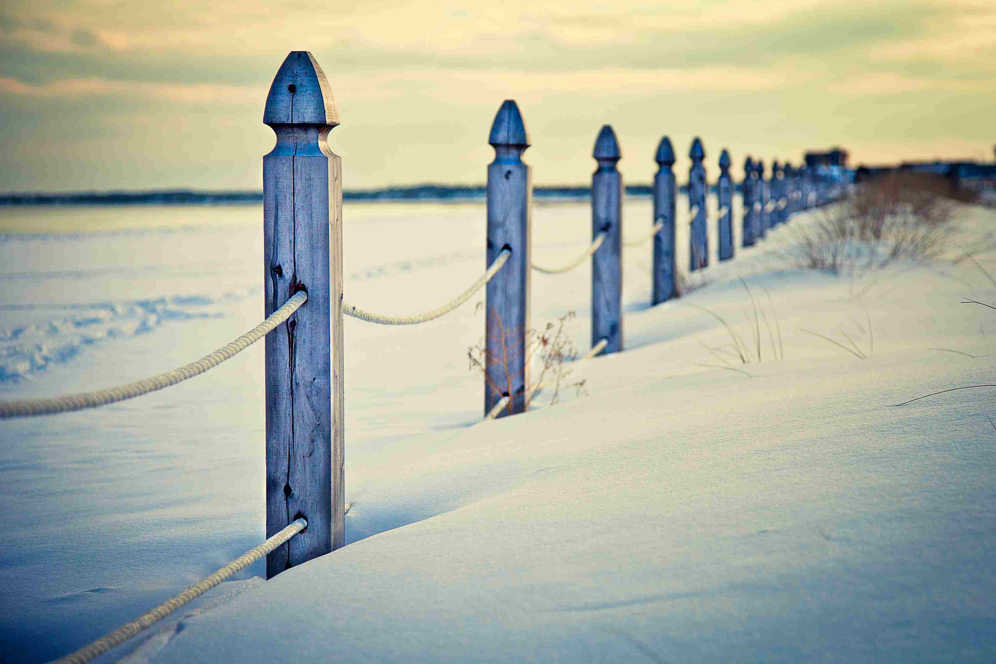 Snowy winter beach of Old Orchard Beach with wooden post fence running diagonally across landscape