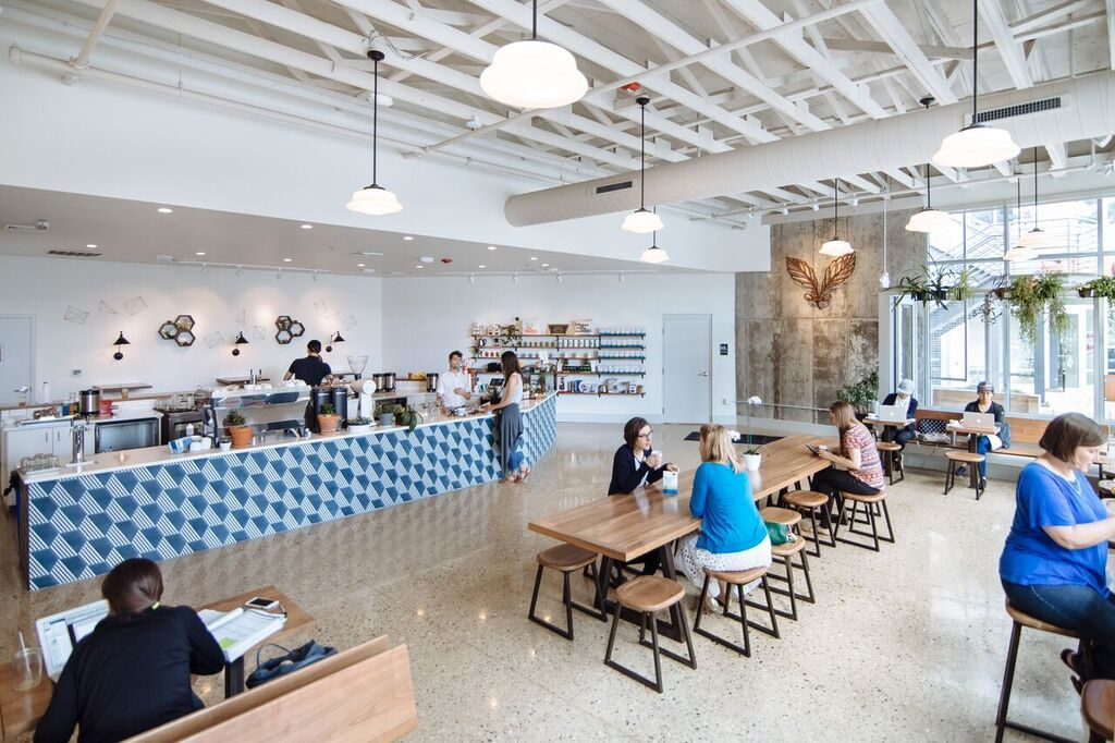Large, airy cafe with an industrial ceiling, a long bar and long wooden tables