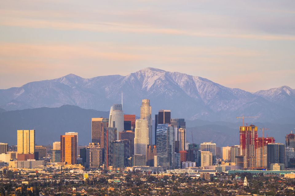 Downtown Los Angeles skyline at sunset with snowcapped Mt Baldy and San Gabriel Mountains behind