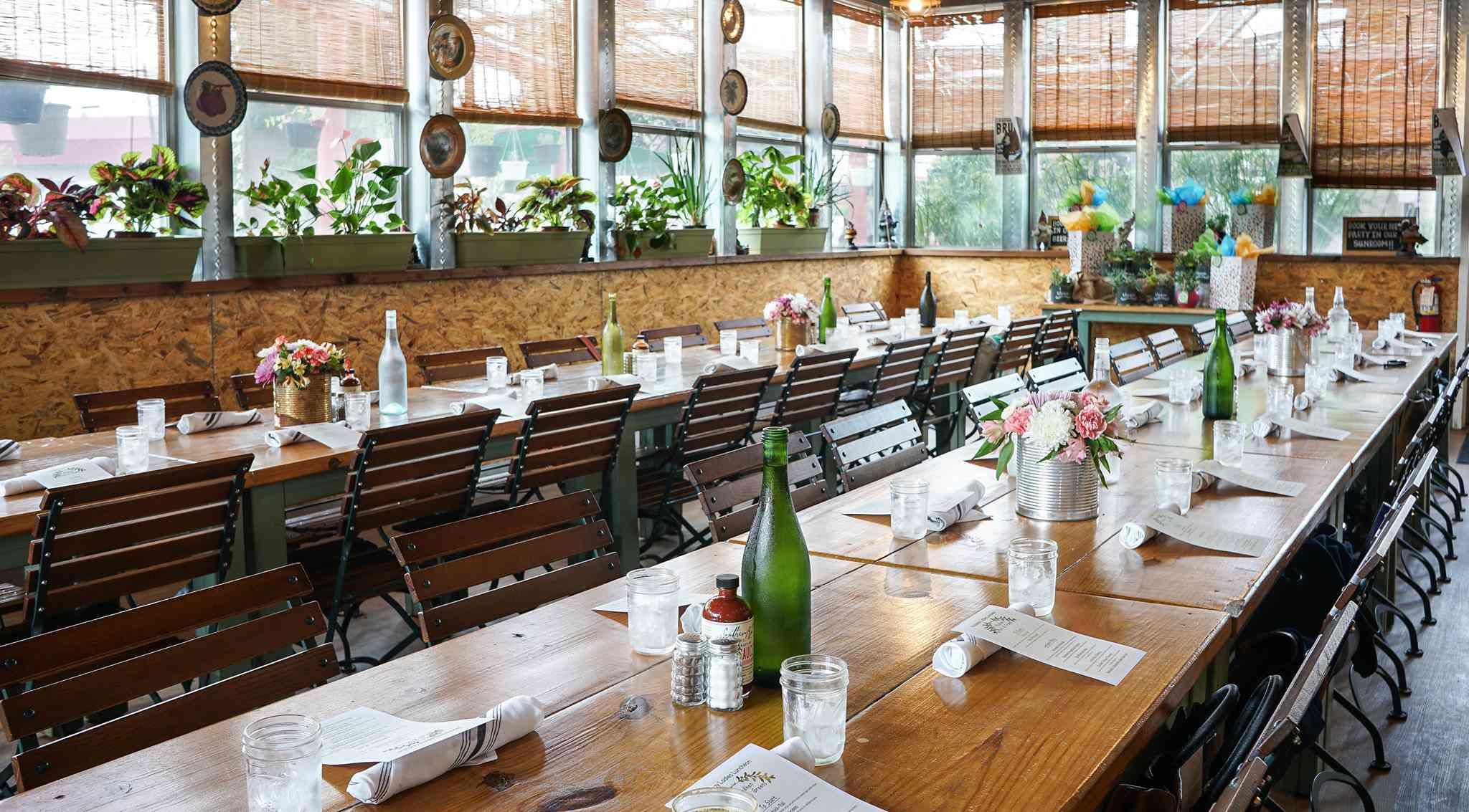 Mesa de comedor larga con cubiertos, flores y botellas de agua verdes