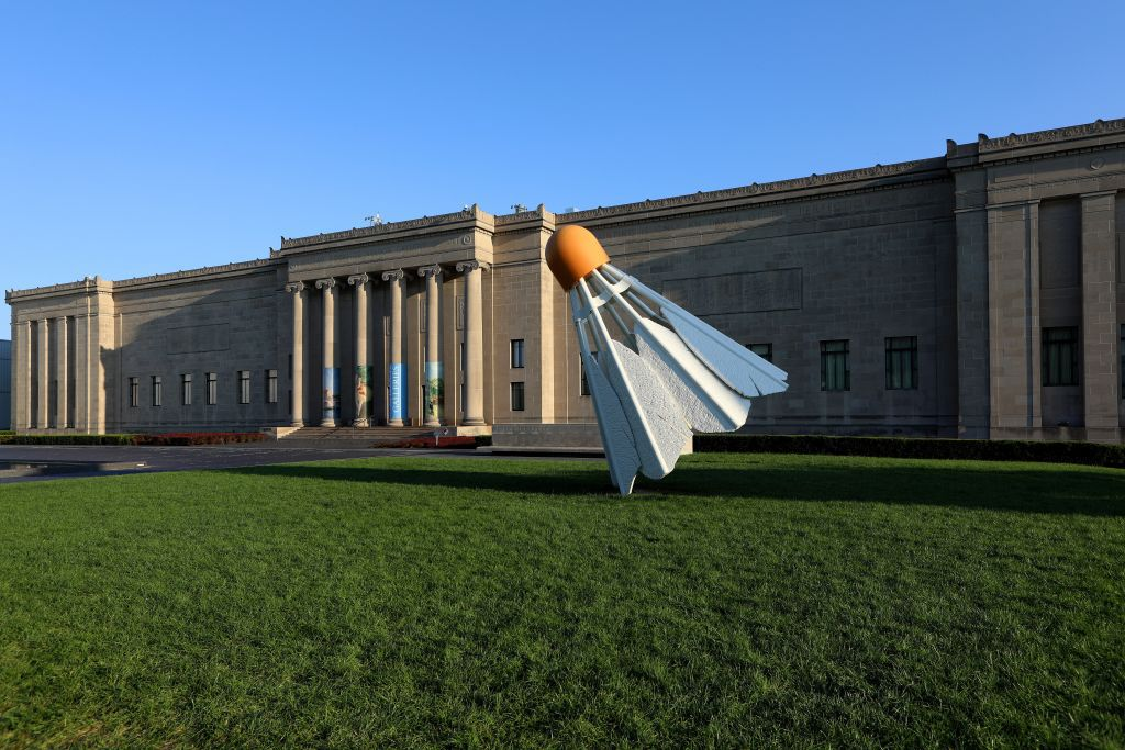 Large statue of a shuttlecock in front of a museum