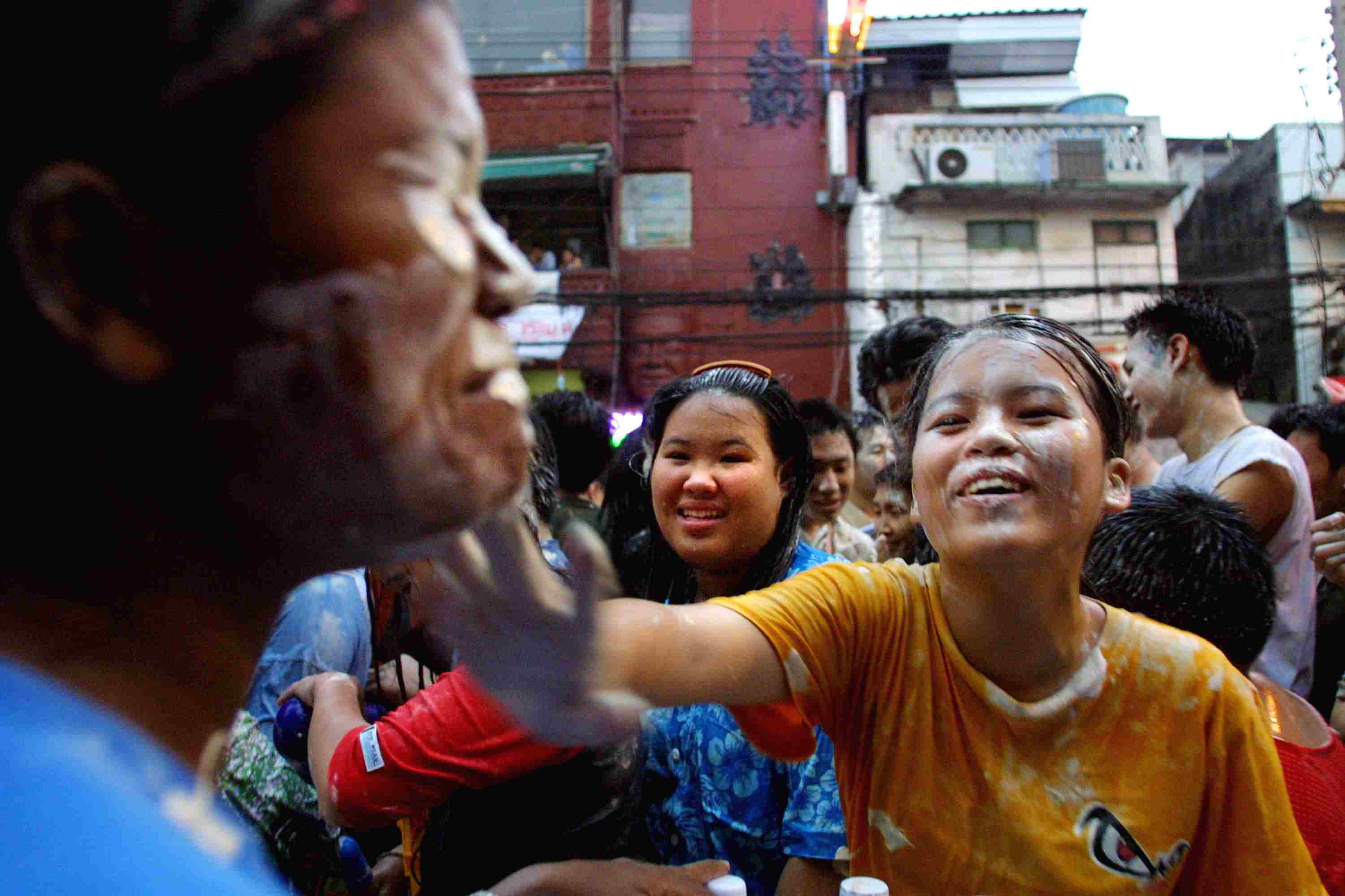 A woman smears a man with white paste during Songkran celebrations