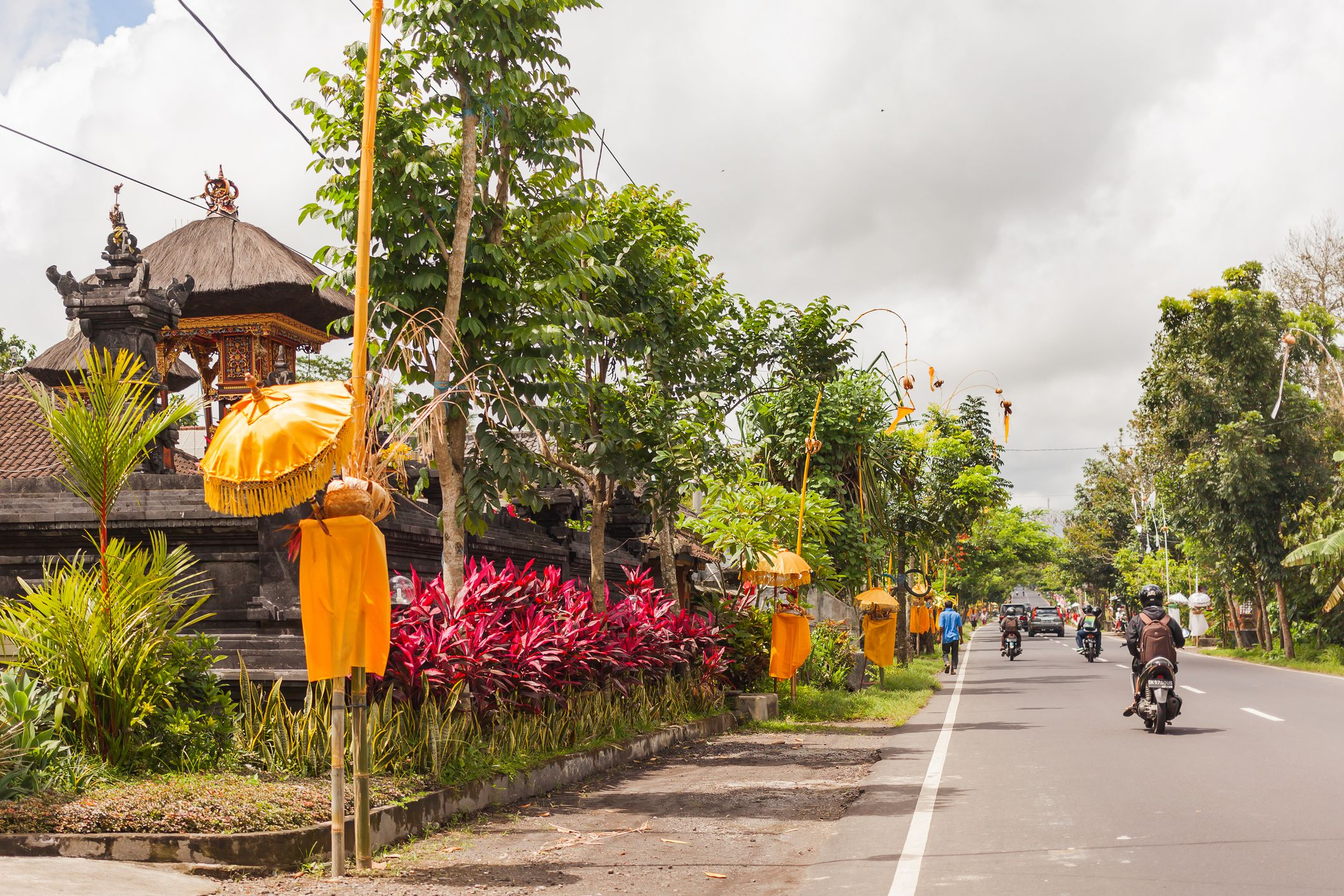 Religious decoration near houses on street. Road traffic in sunny day. Ubud, Bali, Indonesia.
