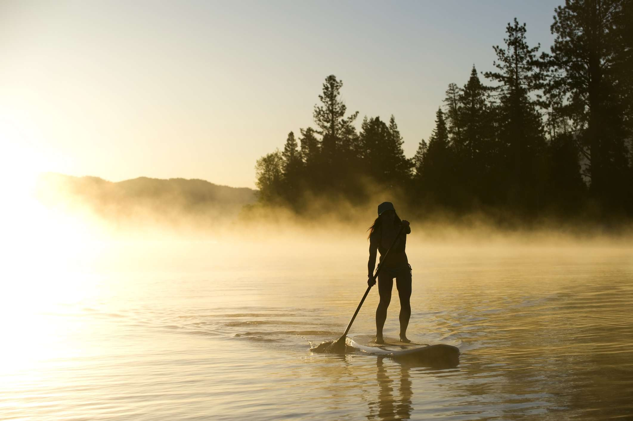 A woman, is silhouetted Stand Up Paddleboarding (SUP) at sunrise in the mist in Lake Tahoe, CA.