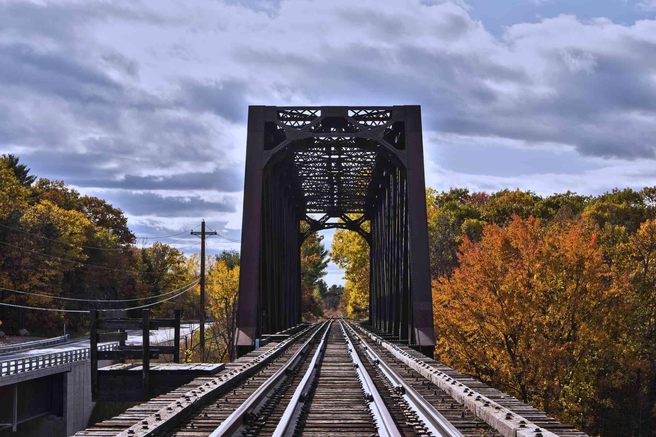 Train tracks on bridge through fall foliage in Quebec