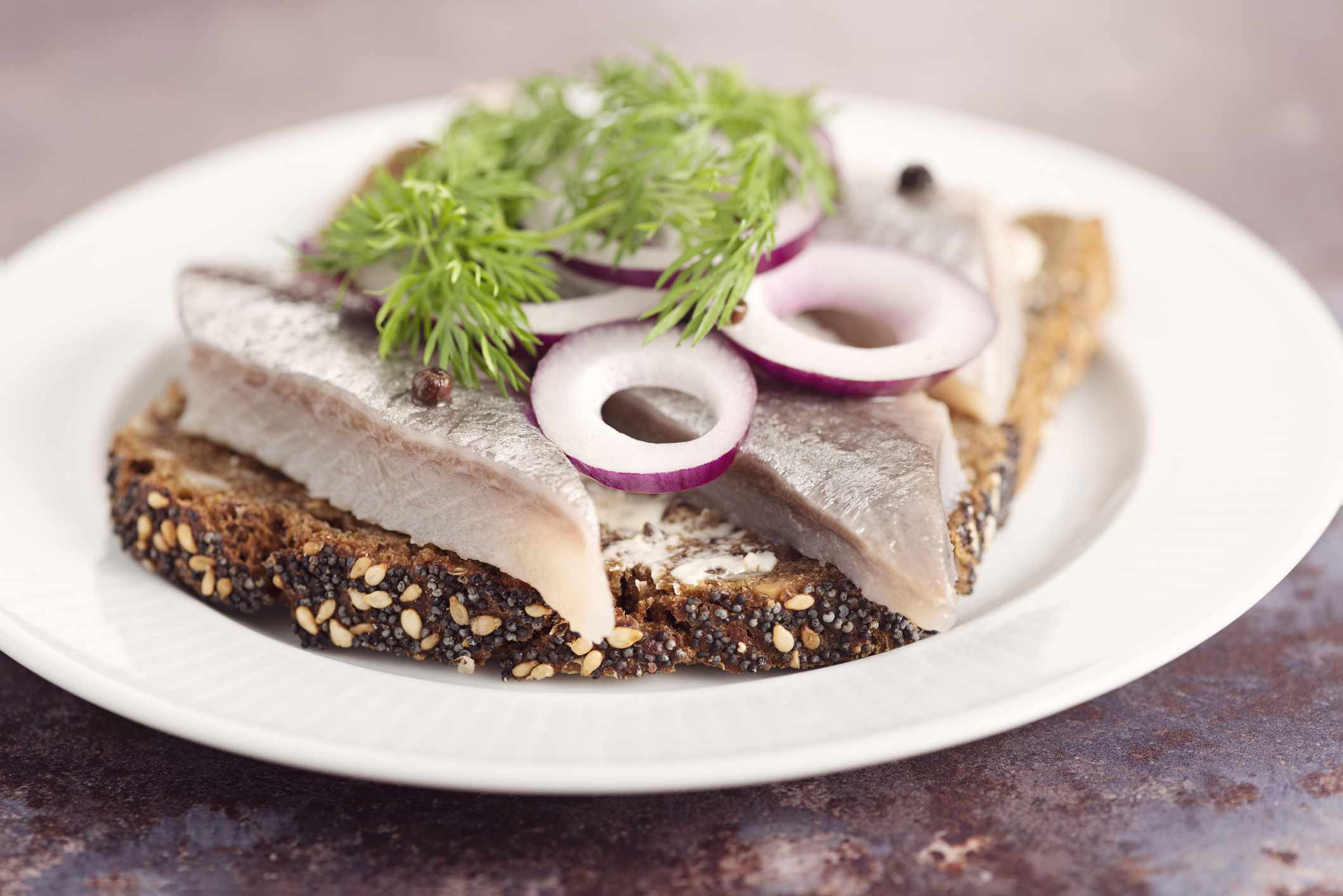 Traditional danish open sandwich made with a slice of buttered rye bread, marinated herring, onion and dill.