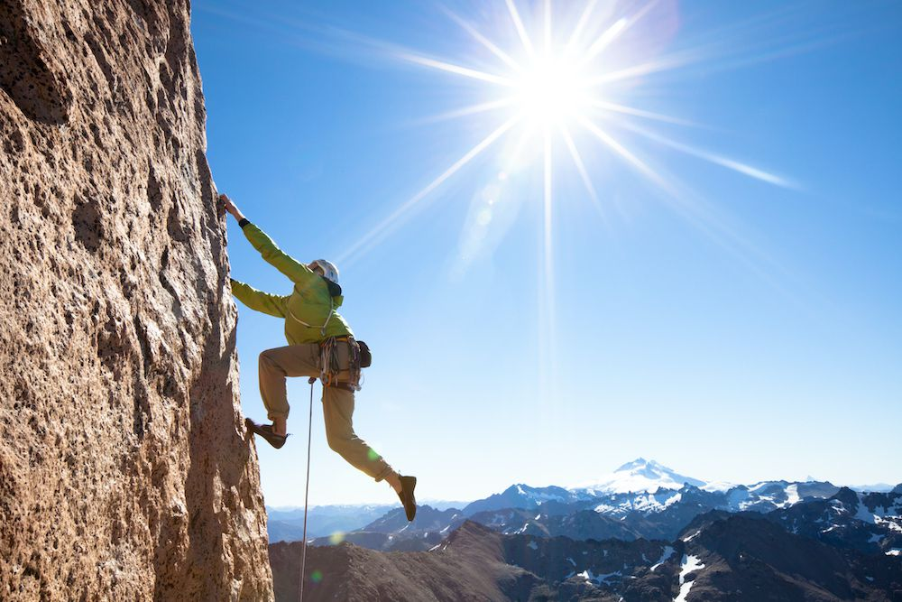 A rock climber goes up a wall with a snowcapped mountain in the background.