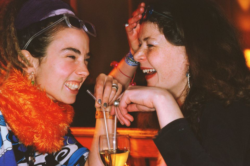 Two women drinking out of the same glass at a bar.