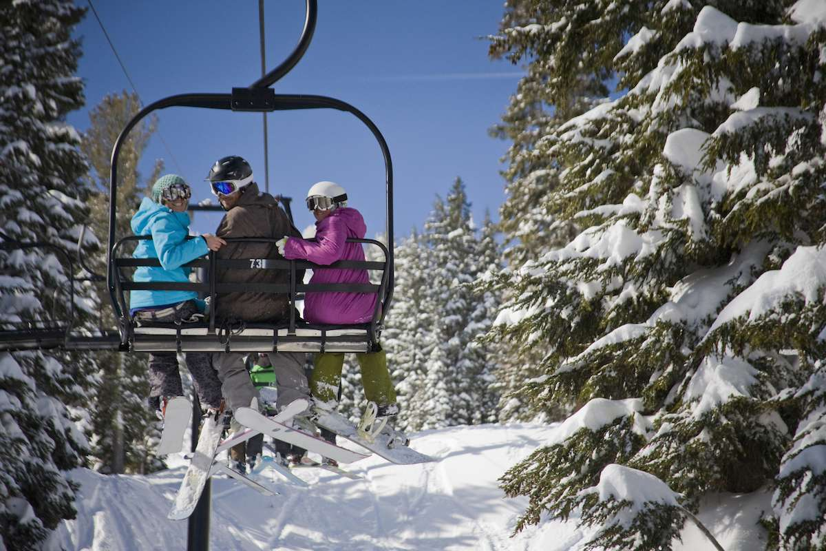 Three skiers ride a lift to the top of the mountain