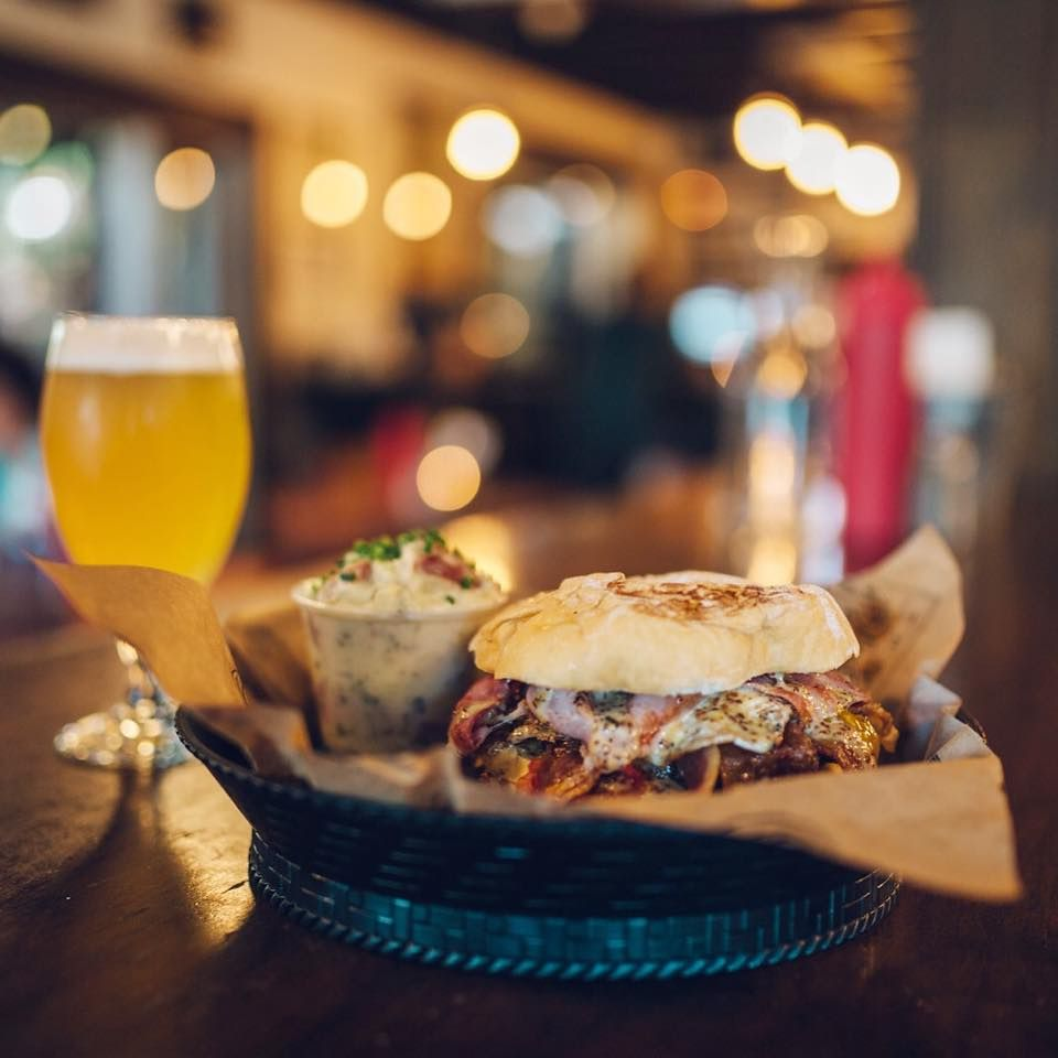Burger in a basket from The Pharmacy with country ham, applewood-smoked bacon, farm egg, maple mustard and a glass of a light-colored beer