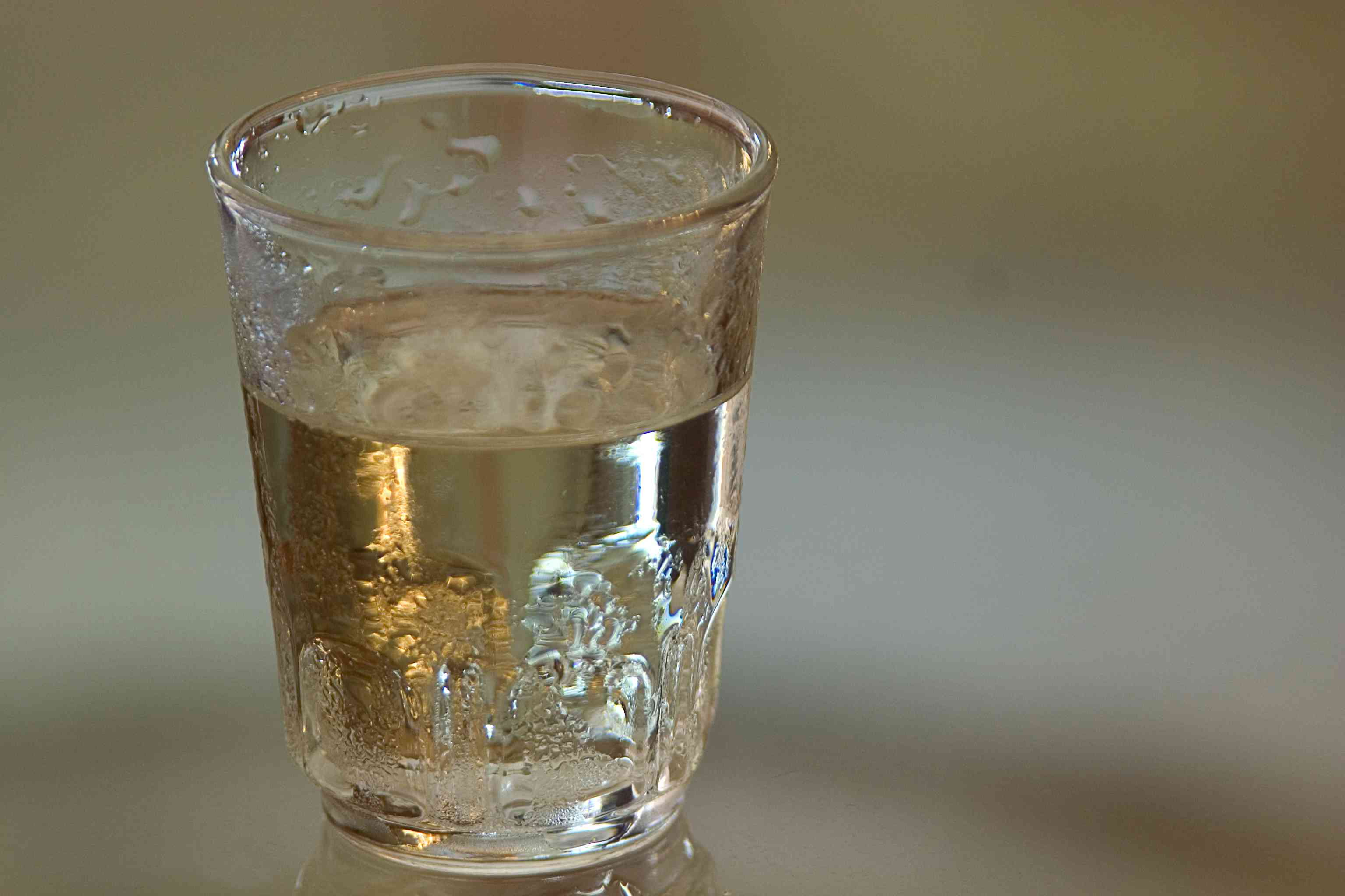 shot of vodka (polish zubrowka actually, that is why it looks a bit dark) right from the fridge, over a glass surface