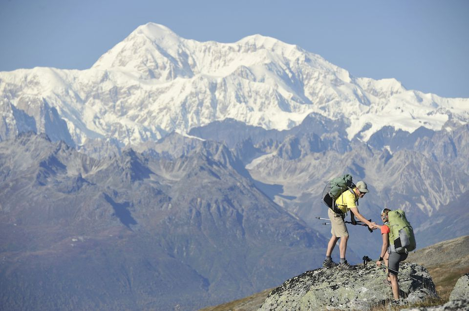 Snowcapped Denali in the background with two hikers on the trail in front.