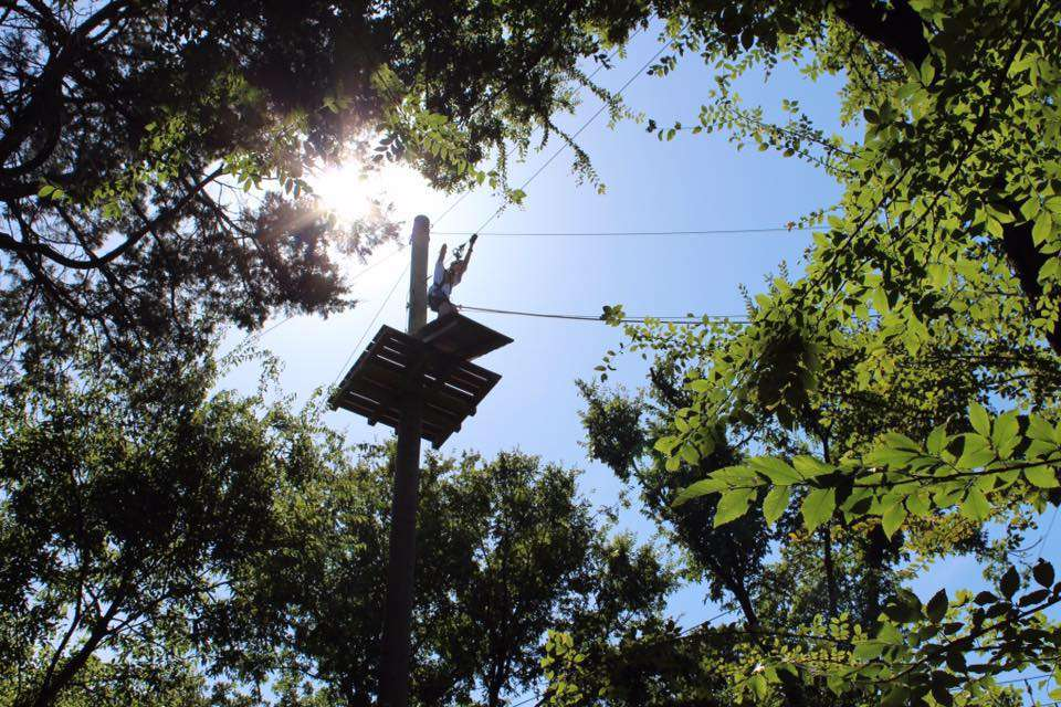 Person standing on a zipline platform photographed from below
