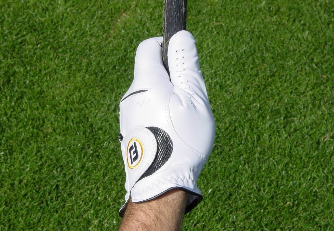 Illustrating thumb position for the top hand in the golf grip