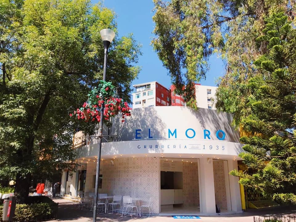 white exteriror of El Moro Polanco with a bright blue El Moro sign. The restaaurant is on a corner and has two tall trees to either side