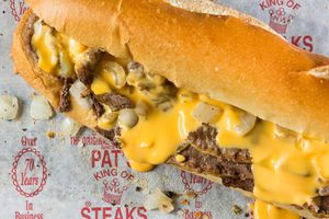 Philly cheesesteak with Cheese Whiz and onion on a paper rhat says