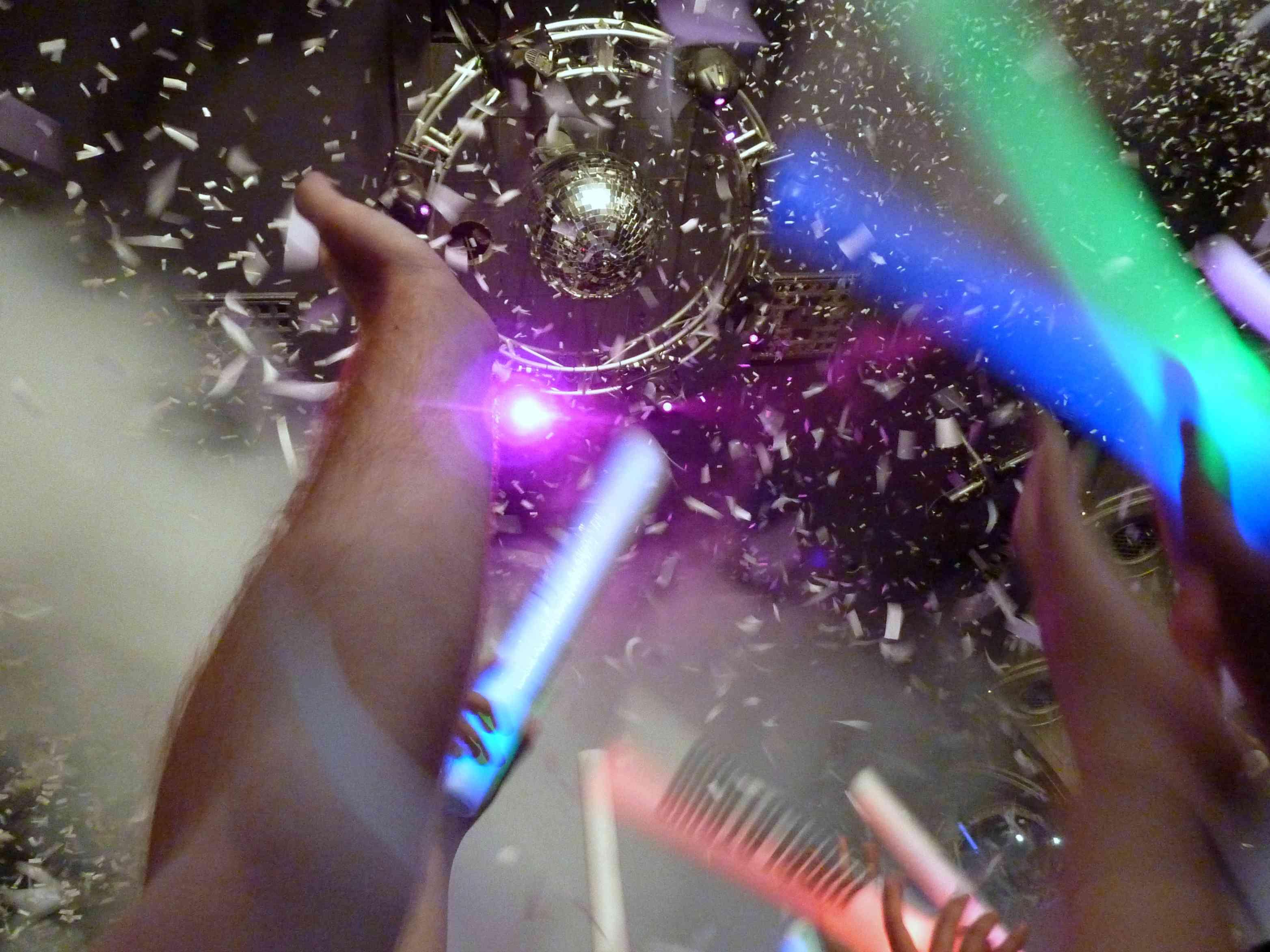 Mano recortada contra el confeti en el club nocturno: fotografía de archivo