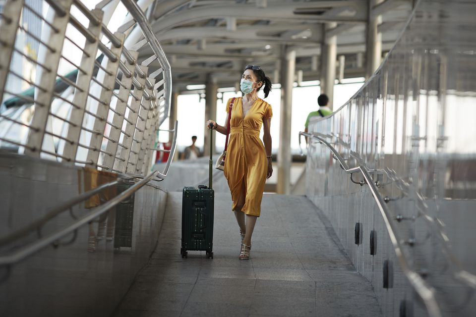 Woman walking with luggage at railroad station