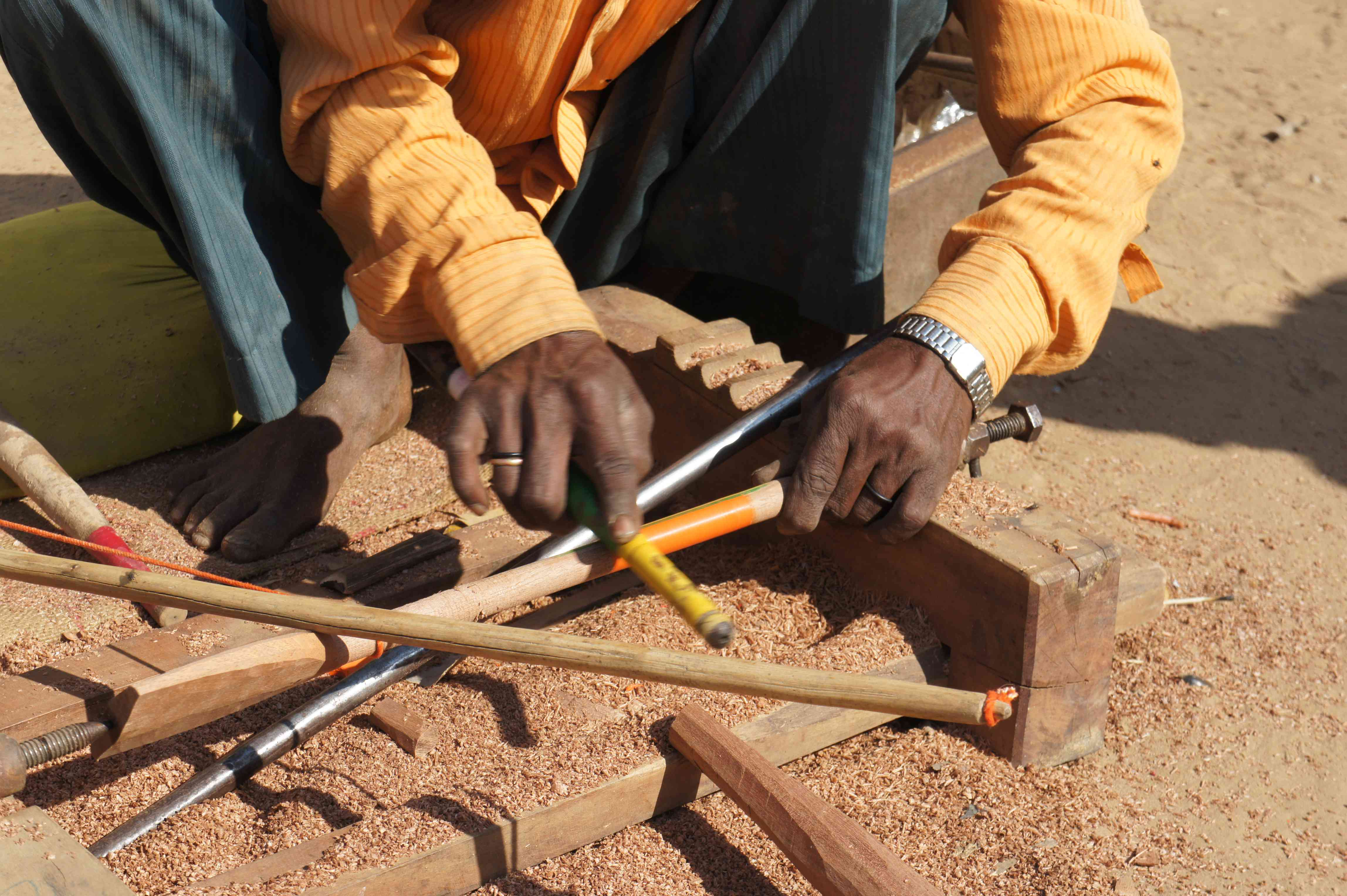 mand useing a lathe to apply color to a piece of wood in Kutch