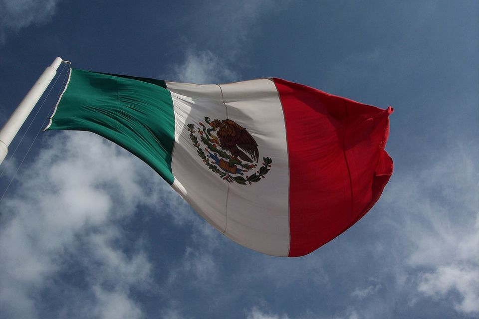 A giant Mexican flag flies against a blue sky