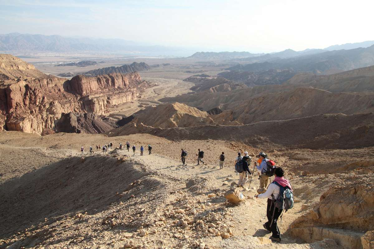 Hikers walk down a trail into the Egyptian arid desert near the Red Sea.
