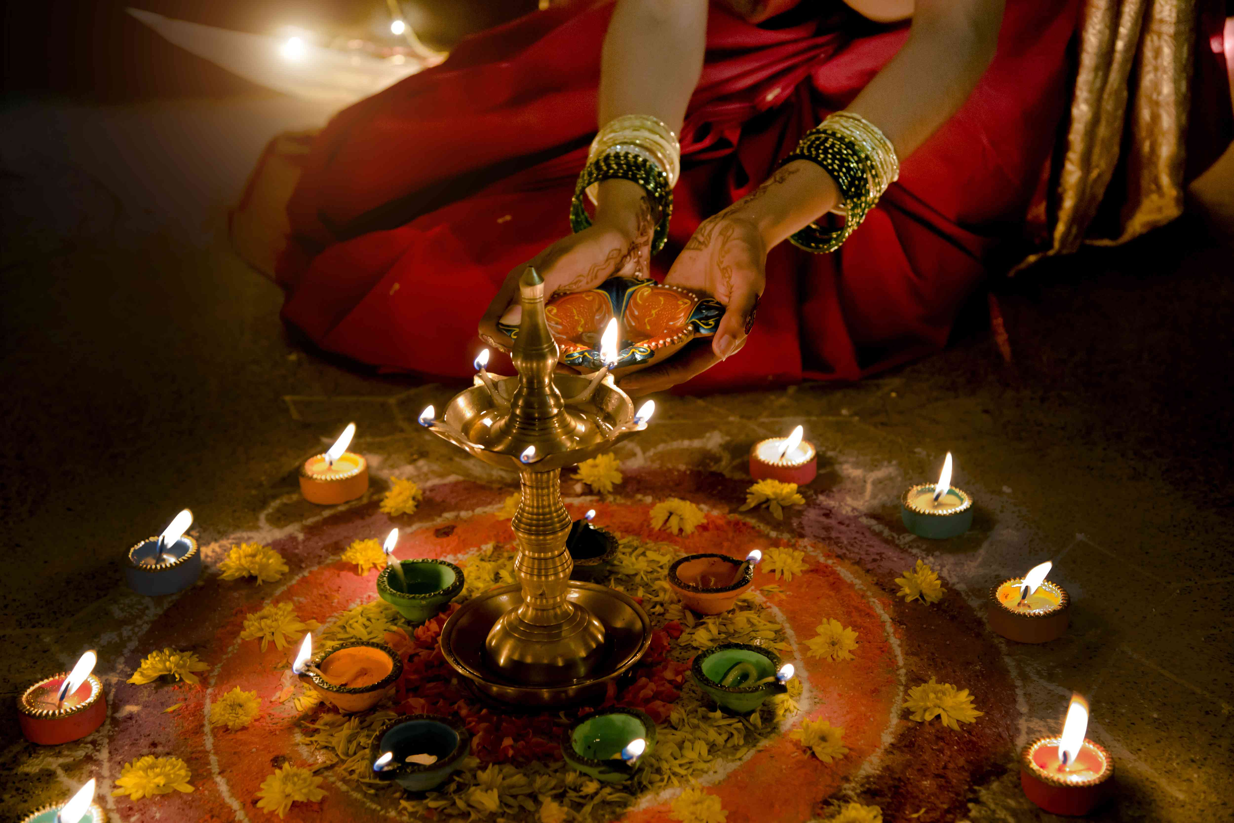 Woman's hands holding a ghee lantern for Diwali in India