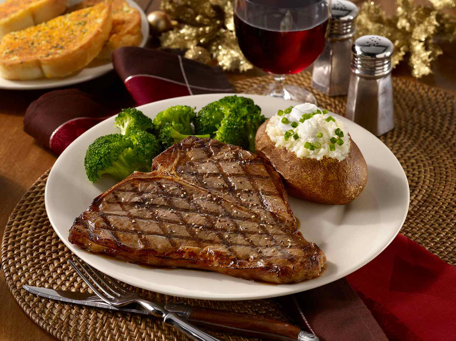 T-bone steak with a loaded baked potato, broccoli, garlic bread and a glass of red wine in a holiday setting.