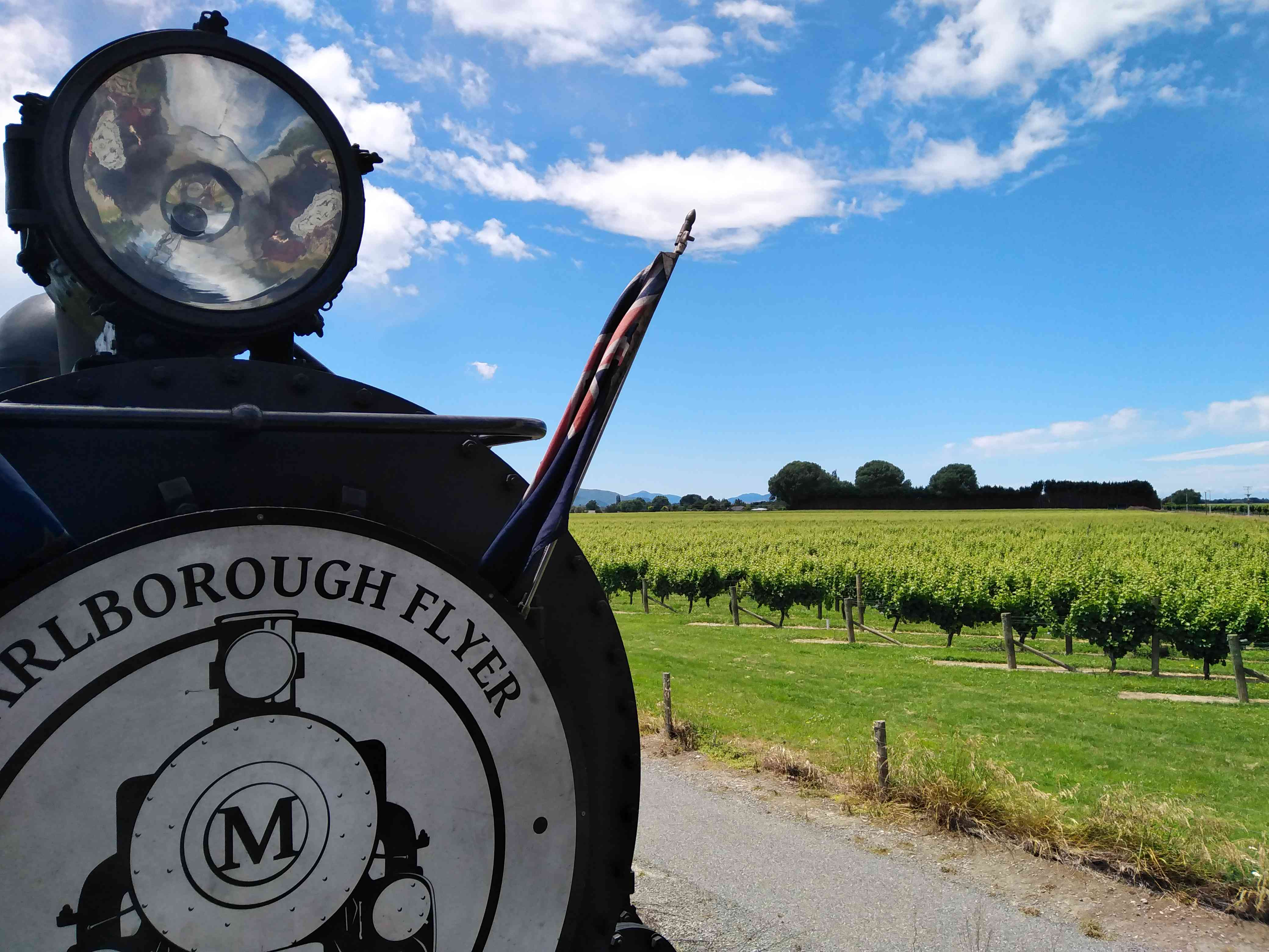 front of steam train with words Marlborough Flyer and vineyards in background