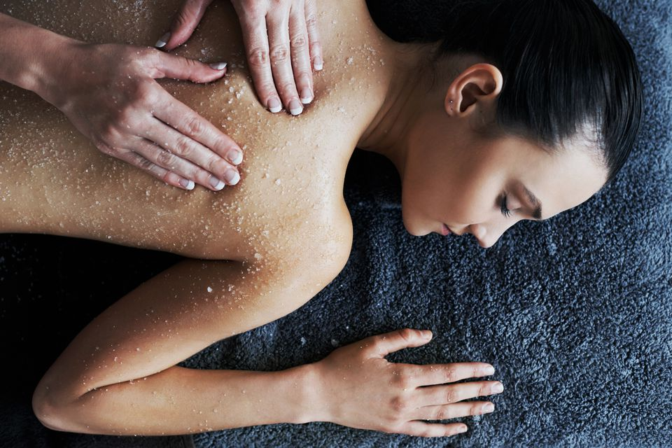 woman getting a body scrub at spa