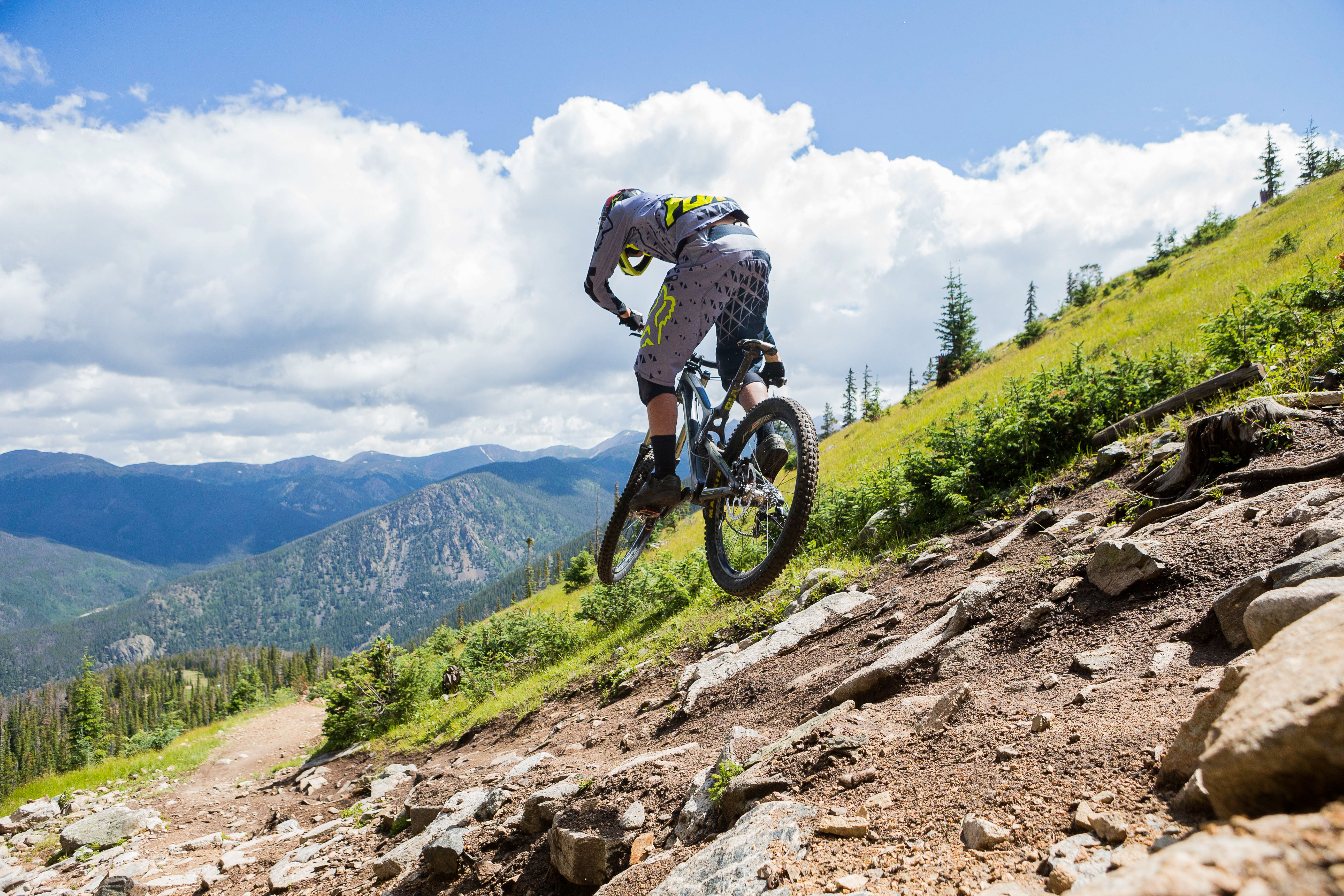 Man performing a downhill jump on a mountain bike