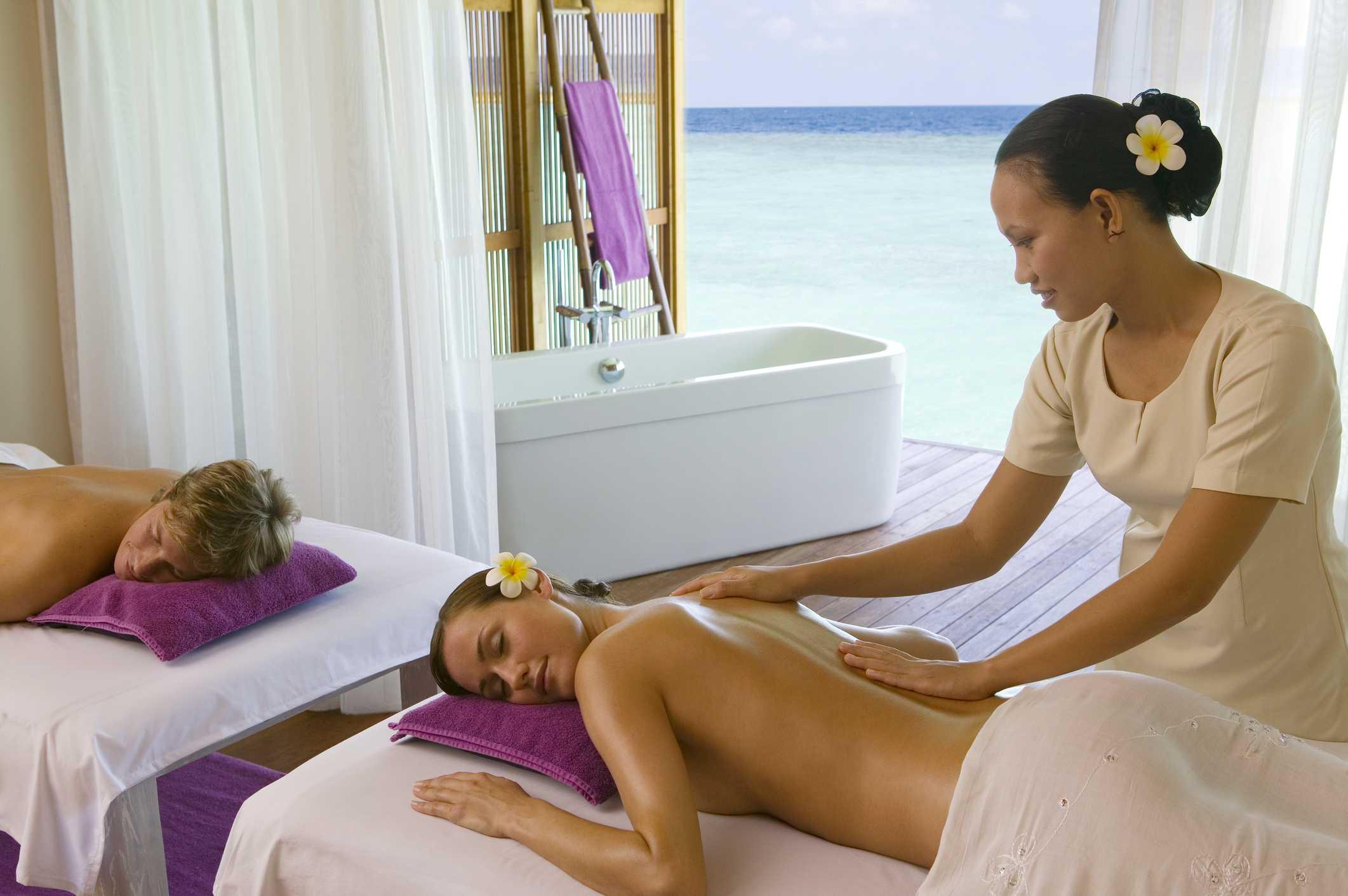 Young couple getting a massage at Veligandu Island Resort, Maldives.
