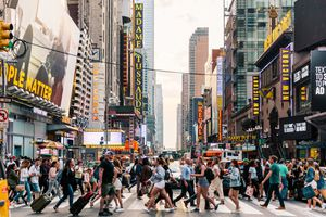 Crowds of people crossing street on zebra crossing in New York, USA