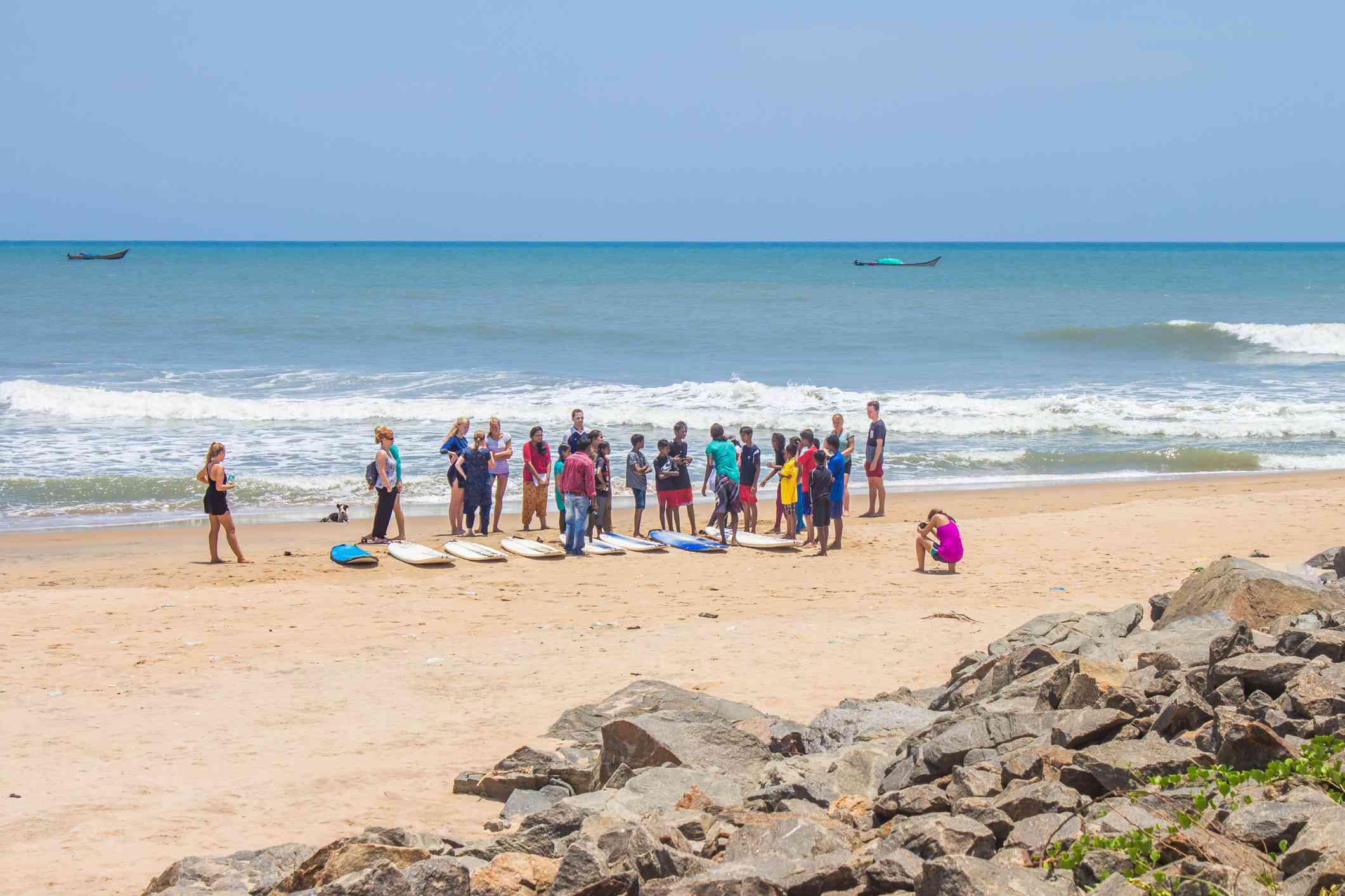 Tourists learn to surf on a beach at Mahabalipuram, Tamil Nadu