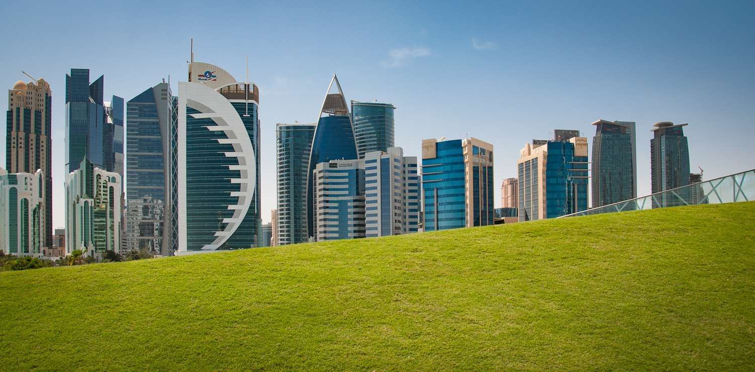 High-rise buildings in Doha behind a green hil