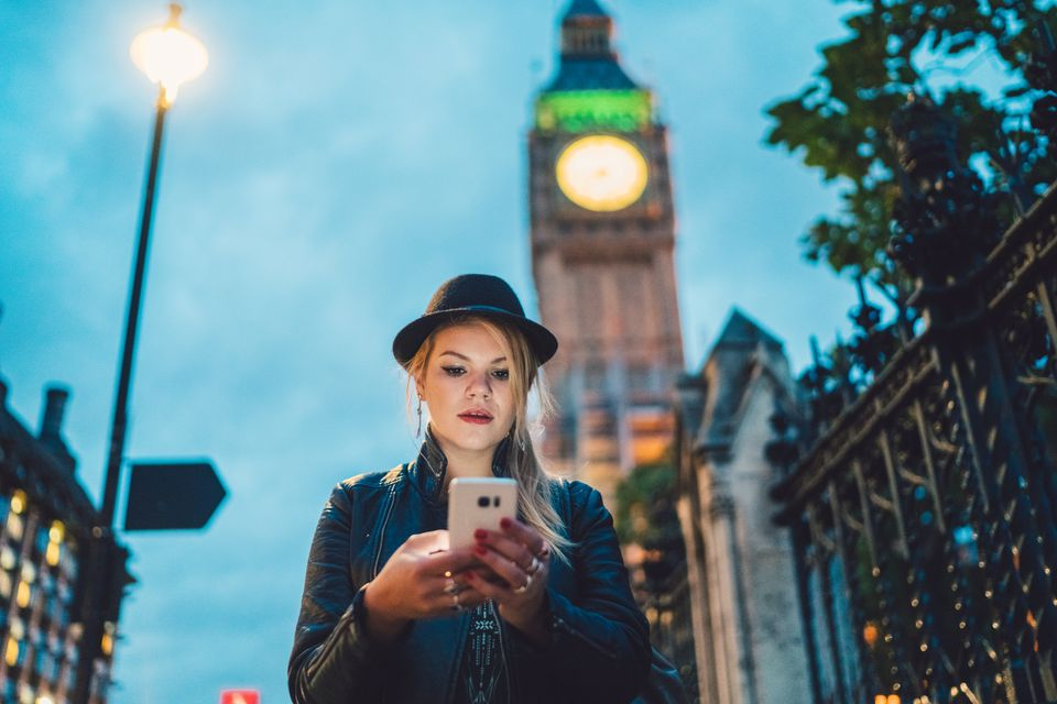 Young woman text messaging at the street in London.