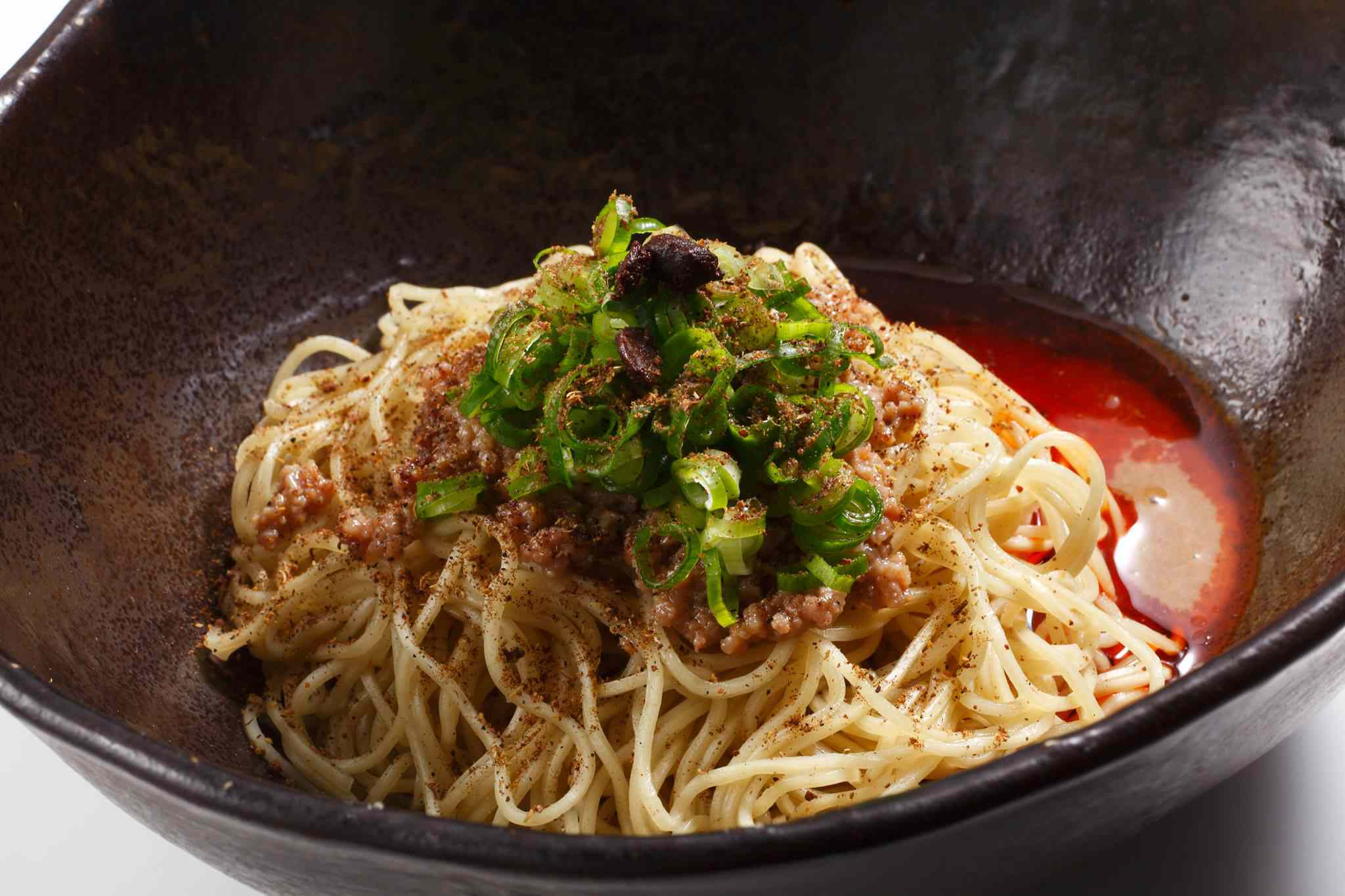 Bowl of noodles topped with seasonings and green onions with a small amount red sauce in the bottom of the bowl