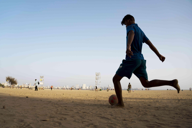Boy playing soccer on Marine Drive beach