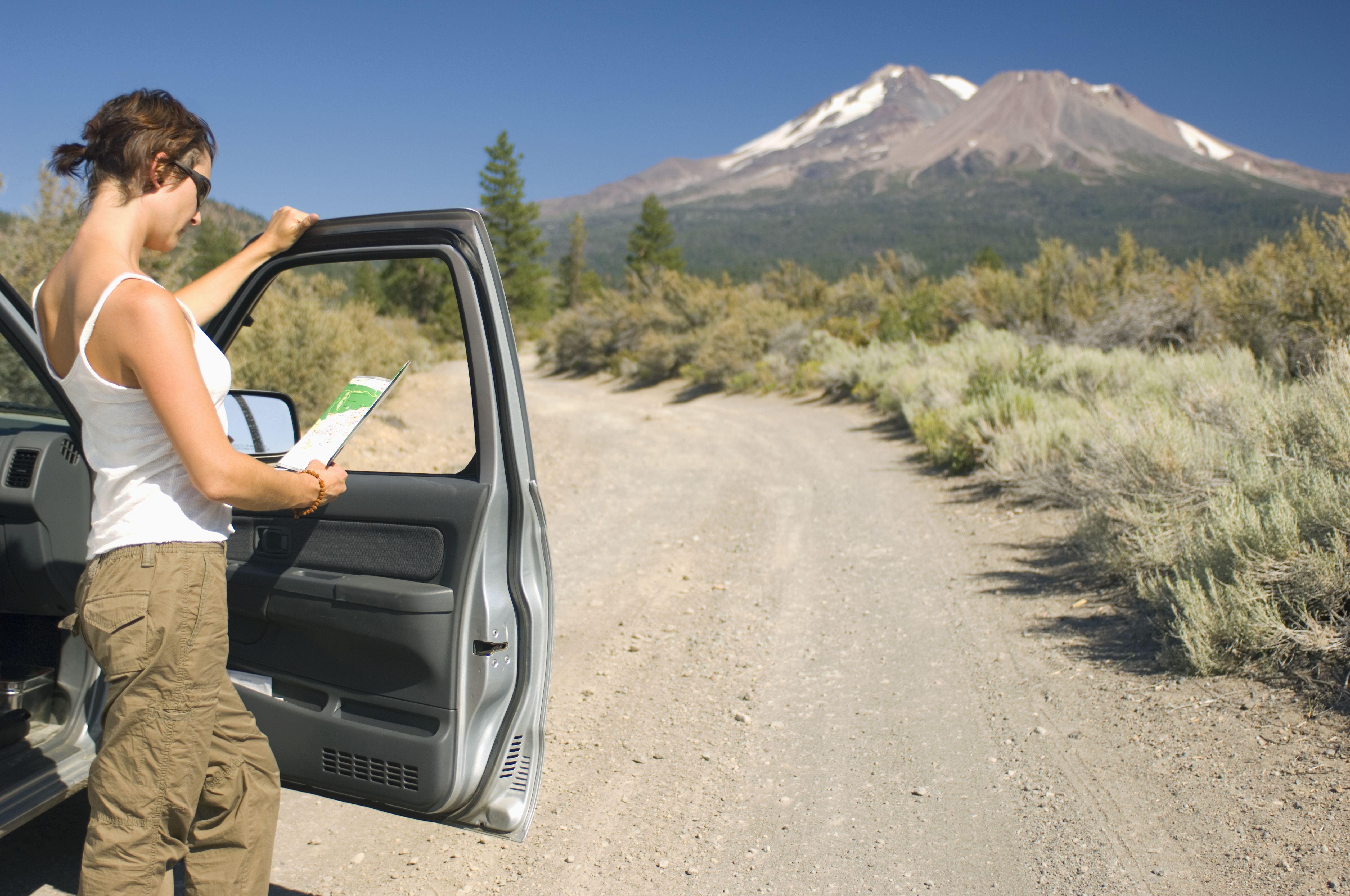 woman looking at map on dirt road at mt shasta