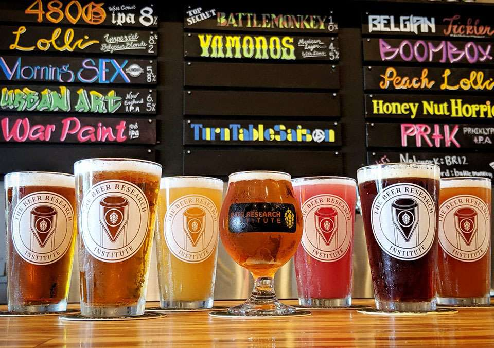 A row of staggered pint classes all filled with different beers and showing the brand logo. The menu of beers on tap sits behind the bar