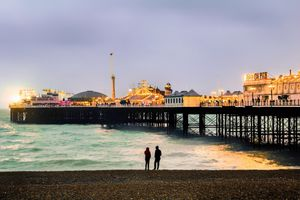 People in Brighton Standing By Sea Against Clear Sky During Sunset