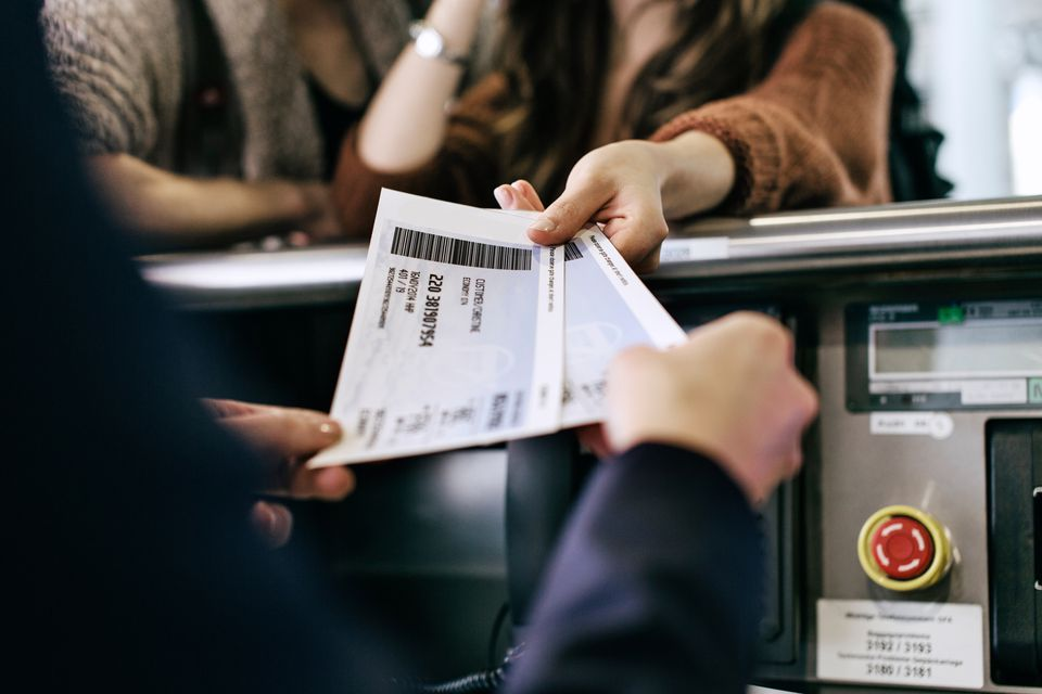 Passenger hands paper tickets to airport employee