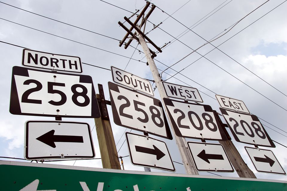 Road signs pointing in different directions, low angle view.