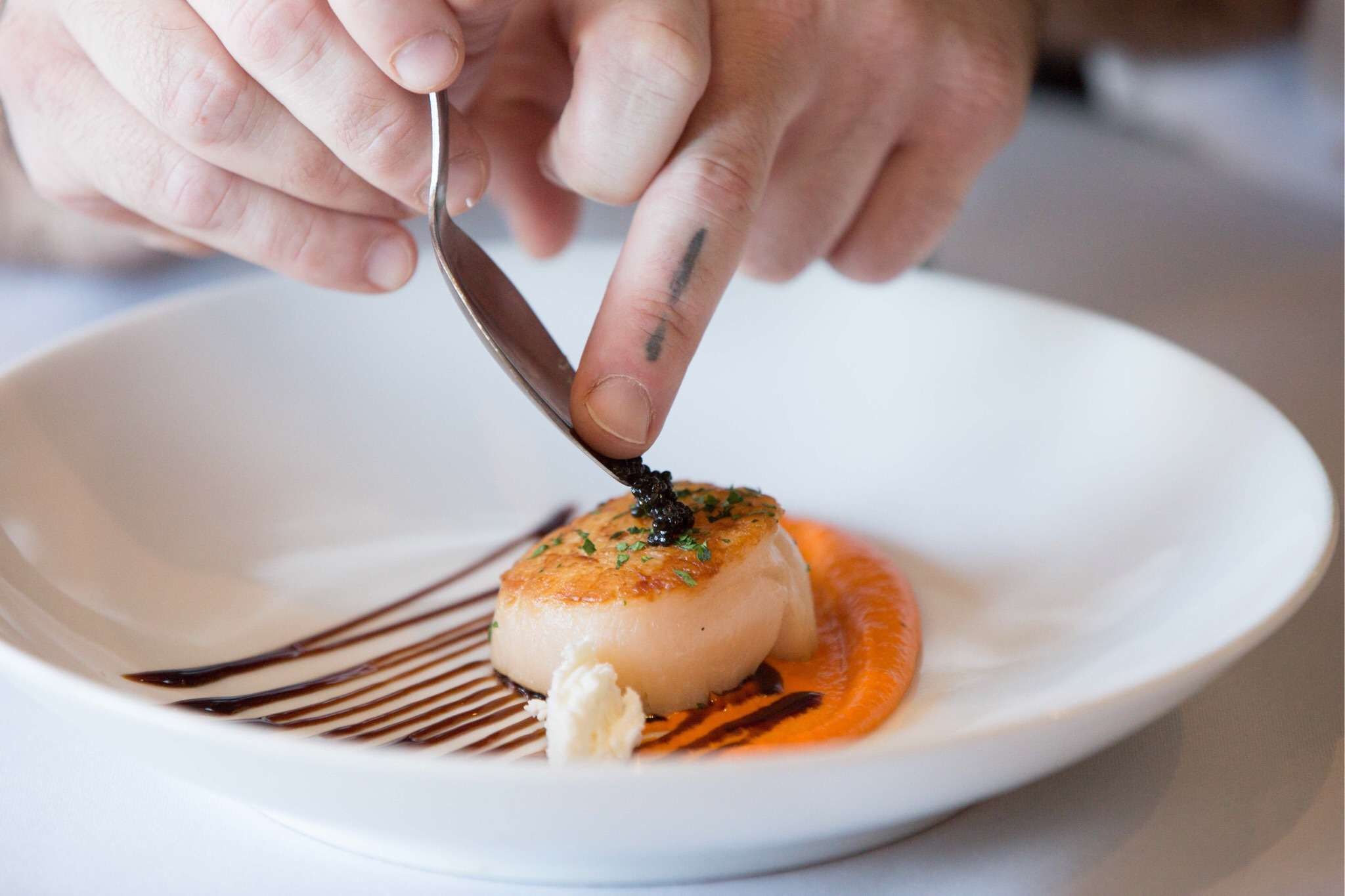 Single scallop on a plate with an orange sauce and a brown sauce as decoration. A pair of hands is transferring caviar from a spoon to the scallop